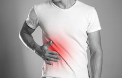 The man is holding his side. Pain in the liver. Cirrhosis. The h stock photo