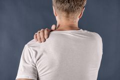 Man holding his sore shoulder trying to relieve pain on blue background. Health problems. Man holding his sore shoulder trying to relieve pain royalty free stock photography