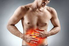Man holding his stomach in pain. Photo of man with naked torso experience stomachaches on grey background. Medical concept Stock Photography