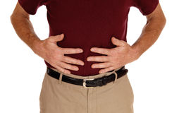 Man holding his stomach for pain. A middle age man in a burgundy t-shirt holding hid stomach for pain in a Royalty Free Stock Photo