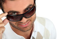 Man holding his sunglasses Stock Photos