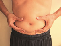 Man is holding his too fat tummy. Of thailand Royalty Free Stock Photography