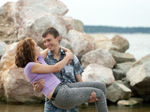 Man is holding his wife on hands outdoors Royalty Free Stock Photo
