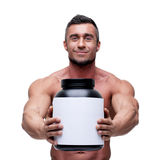 Man holding holding jar with protein. Happy muscular man holding holding jar with protein Royalty Free Stock Photo