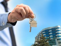 Man holding a home key in his hand and residence background stock images