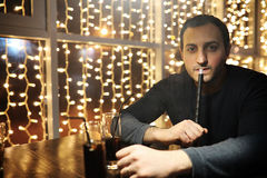 Man holding hookah pipe and smoking in a night club. Handsome man holding hookah pipe and smoking in a night club Royalty Free Stock Photos