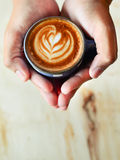 Man holding hot cup of coffee latte art, Stock Photography