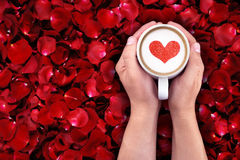 Man holding hot cup of milk on red rose petals background, with red heart shape Royalty Free Stock Photos