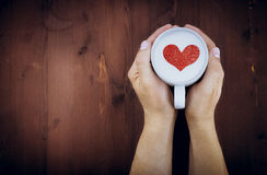 Man holding hot cup of milk on wood table, with red heart shape Royalty Free Stock Image