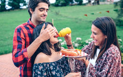 Man holding hot dog in barbecue with friends royalty free stock photo