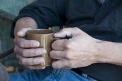 Man holding a hot drink in a mug Stock Photos