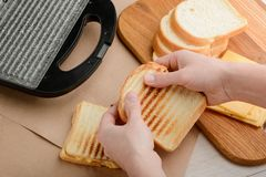 Man holding a hot sandwich. Just from a panini press. Beautiful grilled crust of toast bread. Simple recipe for lunch snack stock images