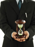 Man holding an hourglass. Close up a man holding an hourglass Stock Images
