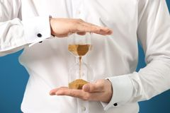 Man holding hourglass, closeup. Time management concept stock photos