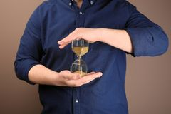 Man holding hourglass on color background. Time management concept royalty free stock images