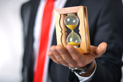 Man holding an hourglass. Man in a suit with tie holding an hourglass Stock Photos