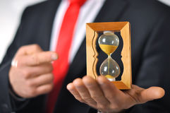 Man holding an hourglass. Man in a suit with tie holding an hourglass Royalty Free Stock Photography