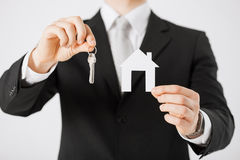 Man holding house keys and paper house Royalty Free Stock Images