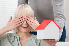 Man Holding House Model In Front Of Smiling Woman Stock Images