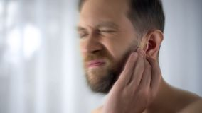 Man holding hurting ear, otitis or infection otolaryngologist problems, close up stock images