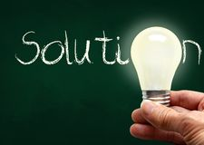 Hand Holding Lighted Bulb With Solution on Chalk Board and Copy Space royalty free stock photography