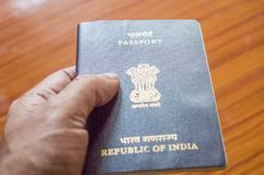 Man holding Indian Passport book over wooden table hardwood floor background, selective focus. Close up. Travel tourism and royalty free stock photos
