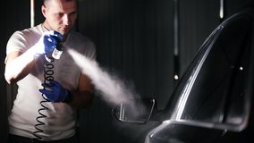 A man holding industrial spray gun for coating the car surface. Mid shot stock footage