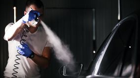 A man holding industrial spray gun for protective coating the car surface. Mid shot stock video