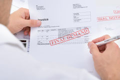 Man Holding Invoice With Final Demand Notification. Close-up Of A Man Holding Invoice With Final Demand Notification And Pen royalty free stock photos