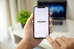 Man holding iPhone X with Internet shopping service Amazon. Alushta, Russia - July 29, 2018: Man holding iPhone X with Internet shopping service Amazon on the stock photography
