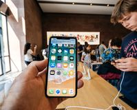 Man holding iPhone X smartphone in Apple Store stock photos