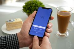 Man holding iPhone X with social networking service VK royalty free stock image