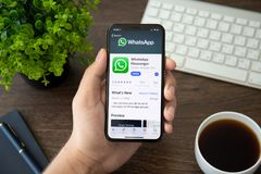 Man holding iPhone X with social networking service WhatsApp. Alushta, Russia - July 30, 2018: Man holding iPhone X with social networking service WhatsApp on royalty free stock photo