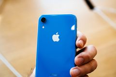 Man holding iphone Xr blue color rear view logo royalty free stock image