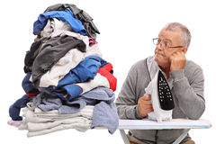 Man holding an iron and looking at pile of clothes Stock Images