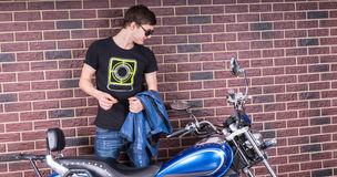 Man Holding a Jacket Looking at his Motorcycle. Attractive Young Man in Shades Holding a Jacket While Looking at his Motorcycle on a Brick Wall Background Royalty Free Stock Image