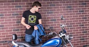 Man Holding a Jacket Looking at his Motorcycle Royalty Free Stock Image