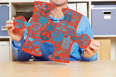 Man holding jigsaw puzzle piece with icons Stock Photography
