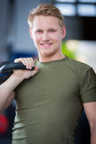 Man holding kettlebell at crossfit center Stock Photos