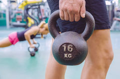 Man holding kettlebell and woman doing pushups in Stock Photo