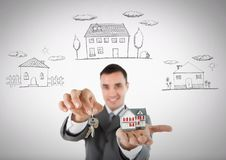 Man Holding key with houses icons and house in front of vignette. Digital composite of Man Holding key with houses icons and house in front of vignette Stock Image
