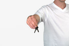 A man holding a key, isolated on a grey background Stock Photography