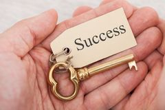 Man holding key with success tag. Closeup of man holding golden key with success tag Stock Image