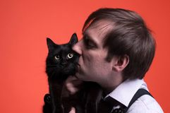 Man holding and kissing on muzzle black cat on orange background royalty free stock photos