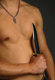 Man holding knife. On a torso Royalty Free Stock Photos