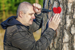 Man holding knife and fabric heart near the tree Stock Images