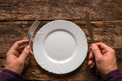 Man holding a knife and fork next to the plate on a wooden Royalty Free Stock Photo