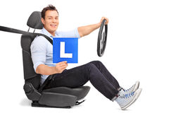 Man holding an L-sign seated on a car seat Royalty Free Stock Photo