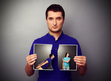 Man holding the lacerated photo of young couple Stock Photo