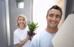 Man holding lamp, woman holding pot plant, smiling, portrait. Man holding lamp, women holding pot plant, smiling, portrait stock photography